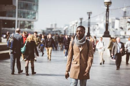ロンドンの背景にぼやけている人々 と、テムズ川の歩道上を歩いて男。彼は離れています。晴れた冬の日に撮影した写真。
