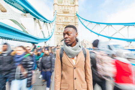 jamaican adult: Man on Tower Bridge, London, with blurred people on background. He is looking away. Photo taken on a sunny winter day. Stock Photo