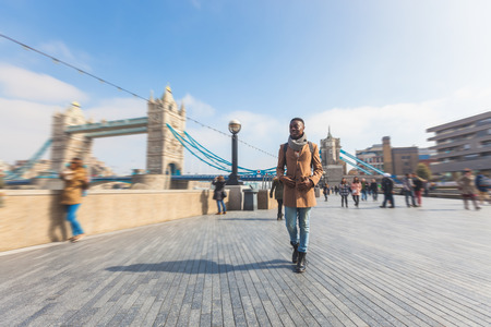 jamaican adult: Man walking in London on Thames sidewalk, with Tower Bridge and blurred people on background. He is looking away. Photo taken on a sunny winter day.