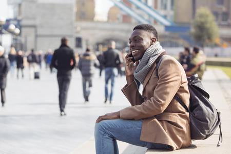 negras africanas: Hombre negro hablando por tel�fono m�vil en Londres. �l est� sentado en un banco de hormig�n, en el fondo hay una gran cantidad de personas borrosas y el Puente de la Torre