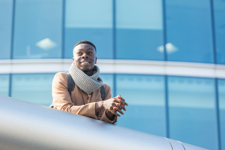 Young black man in London with modern building on background. He wears a vintage coat and scarf and he is looking away from the camera. Stock Photo
