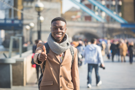 jamaican adult: Successful young black man in London on Thames sidewalk showing thumbs up, with Tower Bridge and blurred people on background.