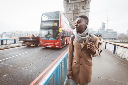 jamaican adult: Young black man in London walking  on Tower Bridge. He wears a brown coat and light blue jeans. Traffic and other persons on background. Stock Photo