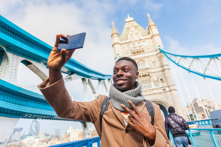 city people: Smiling black man taking selfie in London with Tower Bridge on background. He is holding the phone and looking at camera. Photo taken on a sunny winter day.