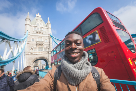 london people: Smiling black man taking selfie in London with Tower Bridge on background. He is holding the phone and looking at camera. Photo taken on a sunny winter day.