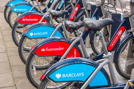 docking: LONDON, UK - MARCH 31, 2015: Cycle hire docking station with new bikes sponsored by Santander who replaced Barclays as main sponsor.