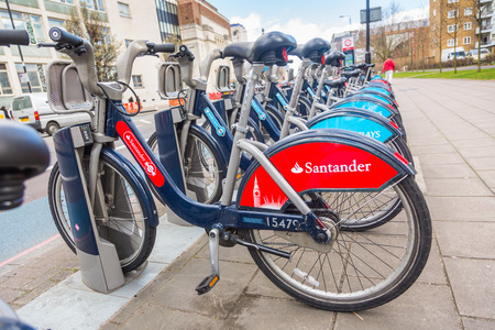 santander: LONDON, UK - MARCH 31, 2015: Cycle hire docking station with new bikes sponsored by Santander who replaced Barclays as main sponsor.