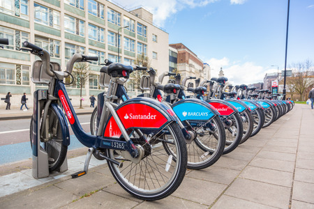 replaced: LONDON, UK - MARCH 31, 2015: Cycle hire docking station with new bikes sponsored by Santander who replaced Barclays as main sponsor.
