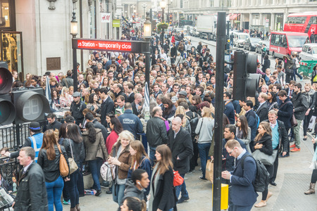 LONDON, UK - APRIL 08, 2015: Crowded Oxford Circus Station entrance due to severe delays in the tube Central Line. Lots of commuters and tourists waiting on the street to enter the station.