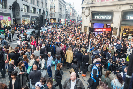 commuters: LONDON, UK - APRIL 08, 2015: Crowded Oxford Circus Station entrance due to severe delays in the tube Central Line. Lots of commuters and tourists waiting on the street to enter the station.