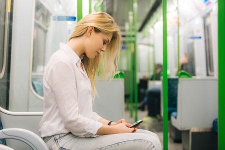 tren: Joven y bella mujer rubia escribir en el tel�fono inteligente en el tubo de tren de Londres. Ella est� sentado, vestido con una camisa blanca y que mira el m�vil.
