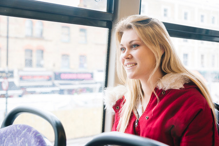 looking out: Beautiful young woman in London on a double-decker bus. She is sitting next to the window and looking out, with buildings and traffic on background.