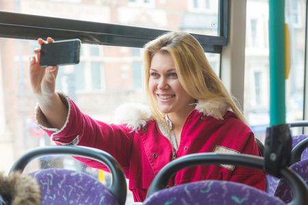 Beautiful young woman taking a selfie while commuting in London with double-decker bus. She is sitting next to the window with buildings and traffic on background. photo