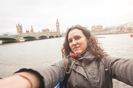 earmuff: Beautiful woman taking a selfie in London with Big Ben and Westminster House of Parliament on background. Stock Photo
