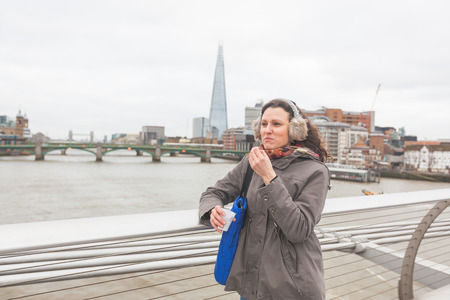 earmuff: Beautiful woman eating roasted peanuts on London Millennium bridge with Shard skyscraper on background.