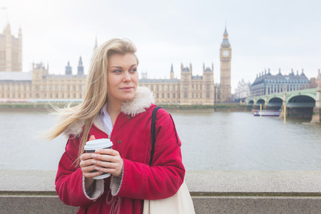 Beautiful blonde young woman holding cup of tea in London  photo