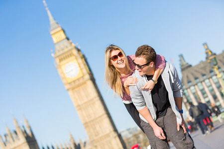 Happy young couple enjoying a piggyback ride in London with Big Ben amd Westminster palace on background.