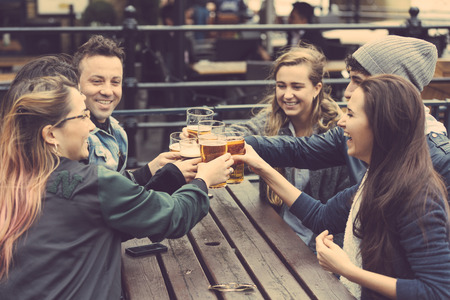 girl friends: Group of friends enjoying a beer at pub in London, toasting and laughing. They are four girls and two boys in their twenties.