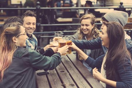 hombre tomando cerveza: Grupo de amigos disfrutando de una cerveza en el pub en Londres, tostar y riendo. Son cuatro niñas y dos niños en sus veinte años. Foto de archivo