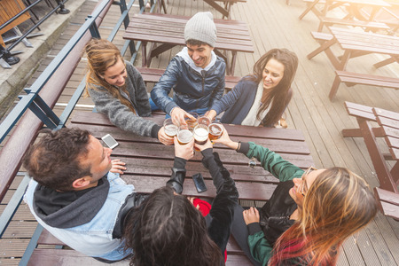 Group of friends enjoying a beer at pub in London, toasting and laughing. They are four girls and two boys in their twenties. photo