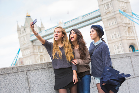 Multiracial group of girls taking a selfie in London with Tower Bridge on background.