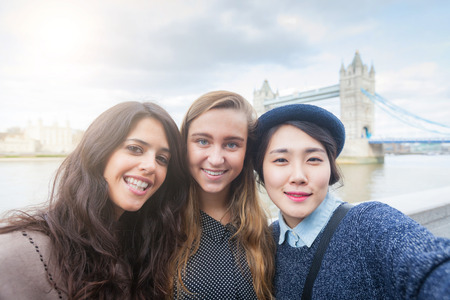 tower of london: Multiracial group of girls taking a selfie in London with Tower Bridge on background.