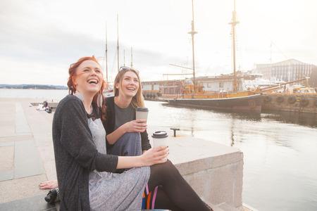Twee mooie nordic meisjes bij de haven van Oslo genieten van het leven, praten en kijken naar slimme telefoon, met schepen op de achtergrond. Stockfoto