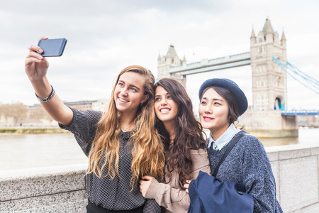 Multiraciale groep meisjes nemen van een Selfie in Londen met de Tower Bridge op de achtergrond. De groep bestaat uit drie meisjes men uit Korea, een uit Spanje en één uit Nederland Stockfoto