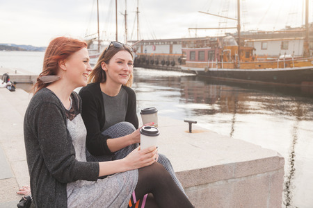 enjoying life: Two beautiful nordic girls at Oslo harbour enjoying life, talking and looking at smart phone, with ships on background.  Stock Photo