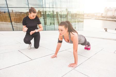 cuerpo femenino: Mujer haciendo flexiones ejerce con su entrenador personal en un contexto urbano moderno.