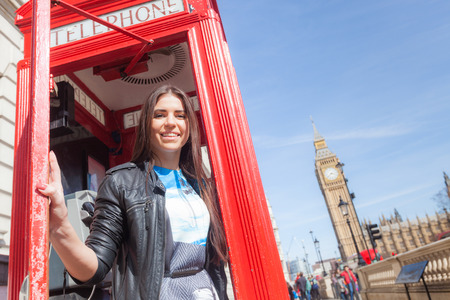 cabina telefonica: Mujer hermosa joven en Londres con el Big Ben y cabina de tel�fono roja en el fondo. Ella est� sosteniendo la puerta abierta y mirando a la c�mara. Centrarse en la cara.