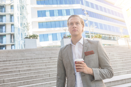 facial features: Fashioned young man in Oslo holding a cup of coffee with buildings on background. He has nordic facial features, and wearing a light gray suit.
