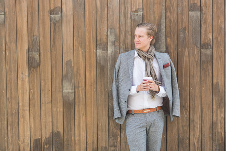 facial features: Fashioned young man in Oslo holding a cup of coffee and leaning on a wooden background. He has nordic facial features, and wearing a light gray suit. Stock Photo