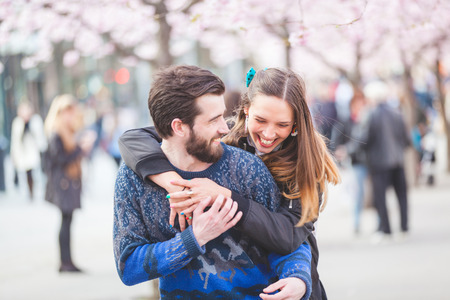 Young hipster couple embracing and smiling in Stockholm with cherry blossoms at Kungstradgarden, the swedish for Kings Garden. Love and friendship concepts with a hipster theme. Archivio Fotografico