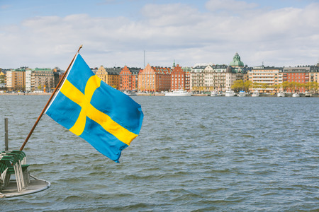 sweden flag: Swedish flag on the rear of a boat in Stockholm, with some colorful houses on the water edge on background.