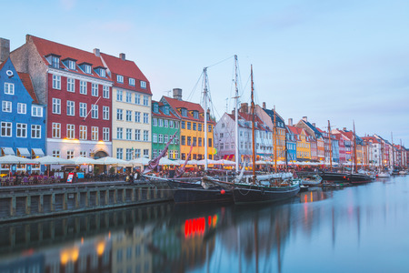 street view: Colorful houses in Copenhagen old town, with boats and ships in the canal in front of them. Long exposure shot in late afternoon. Stock Photo