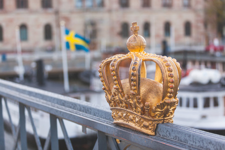 archipelago: Golden crown with swedish flag on background in Stockholm. Stock Photo