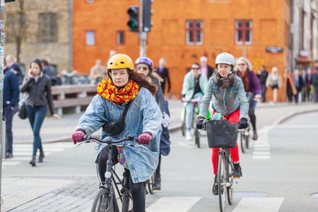to prefer: COPENHAGEN, DENMARK - APRIL 28, 2015: People going by bike in the city. A lot of commuters, students and tourists prefer using bike instead of car or bus to move around the city.