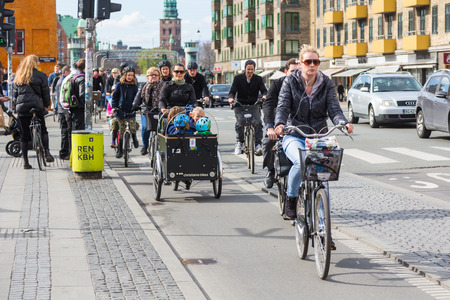 COPENHAGEN, DENMARK - APRIL 28, 2015: People going by bike in the city. A lot of commuters, students and tourists prefer using bike instead of car or bus to move around the city.