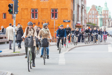 COPENHAGEN, DENMARK - APRIL 28, 2015: People going by bike in the city. A lot of commuters, students and tourists prefer using bike instead of car or bus to move around the city. Reklamní fotografie - 39324561