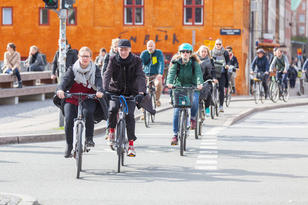 road bike: COPENHAGEN, DENMARK - APRIL 28, 2015: People going by bike in the city. A lot of commuters, students and tourists prefer using bike instead of car or bus to move around the city.