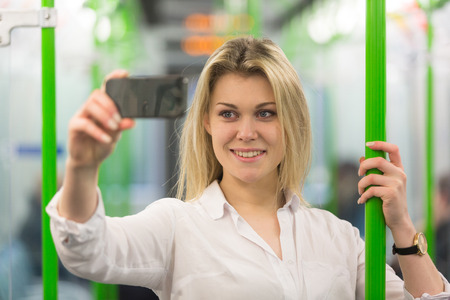 Beautiful blonde young woman taking a selfie with smart phone in London tube train. She is holding to a pole, wearing a white shirt and looking at the phone. photo