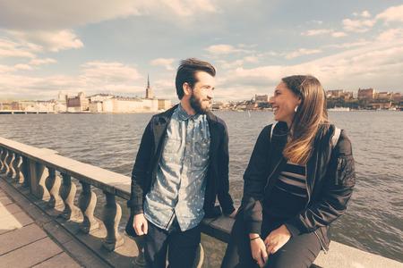 jovenes enamorados: Pareja joven inconformista visitar Estocolmo. Ellos están caminando con el mar y la ciudad vieja en el fondo. Ambos están usando gafas de sol y una chaqueta negro.