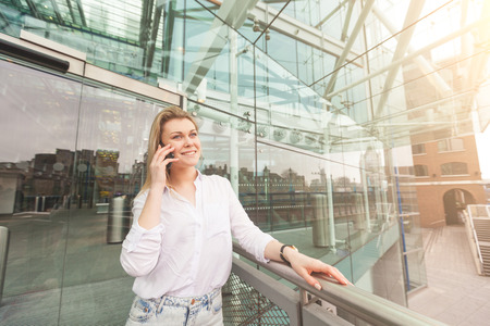 Young woman talking on smart phone in front of a modern glazed building in London. She is blonde, wearing a white shirt and staying by three quarters. photo