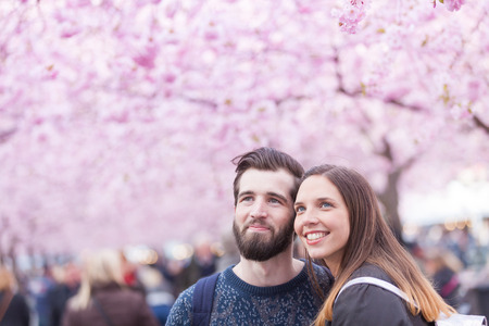 lovers park: Young hipster couple portrait in Stockholm with cherry blossoms at Kungstradgarden, the swedish for Kings Garden. Love and friendship concepts with a hipster theme.
