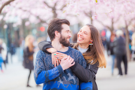 lovers park: Young hipster couple embracing and smiling in Stockholm with cherry blossoms at Kungstradgarden, the swedish for Kings Garden. Love and friendship concepts with a hipster theme. Stock Photo