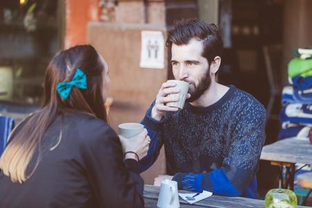 mujer tomando cafe: Pareja Hipster consumo de café en el casco antiguo de Estocolmo. Están sentados cara a cara. El hombre viste un suéter azul y la mujer una camisa a rayas con chaqueta de cuero negro. Foto de archivo