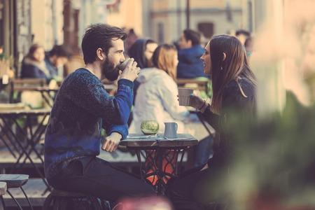 stile di vita: Hipster paio di bere il caffè in città vecchia di Stoccolma. Sono seduti faccia a faccia. L'uomo indossa un maglione blu e la donna una camicia a strisce con giacca di pelle nera. See-through colpo.