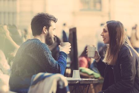 hombre tomando cafe: Pareja Hipster consumo de caf� en el casco antiguo de Estocolmo. Est�n sentados cara a cara. El hombre viste un su�ter azul y la mujer una camisa a rayas con chaqueta de cuero negro. Ver a trav�s de tiro.