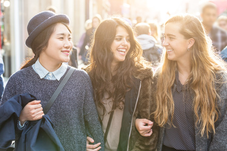 korea girl: Multiracial group of girls walking in London. Urban background with busy road and sidewalk, friendship and lifestyle concepts. Group consists of one girl from Korea, one from Spain and one from Holland Stock Photo